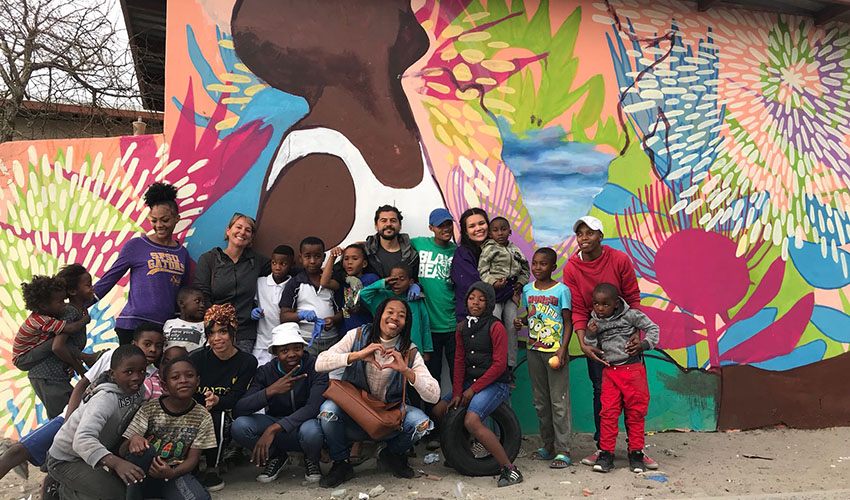 Students and Vrygond community members in front of mural