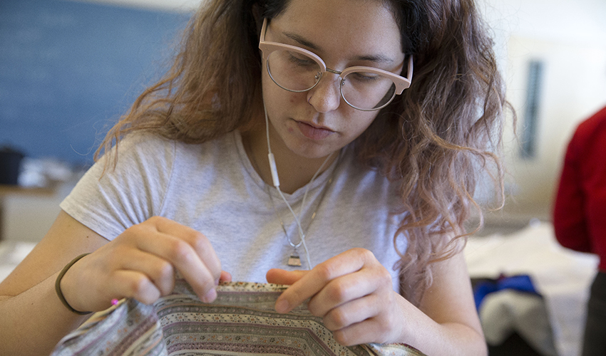 Design student sews fabric for her collection