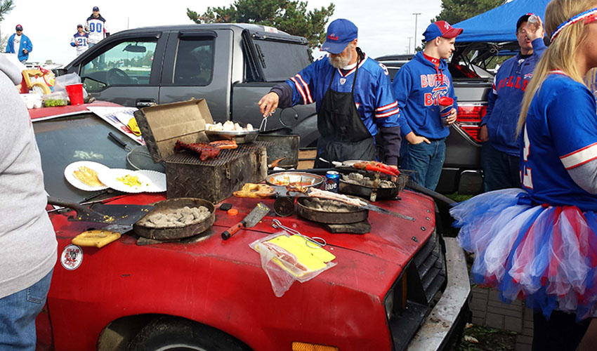 Tailgaters grill on a car