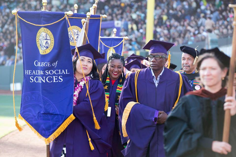 Grads at 2017 Commencement carry College banner