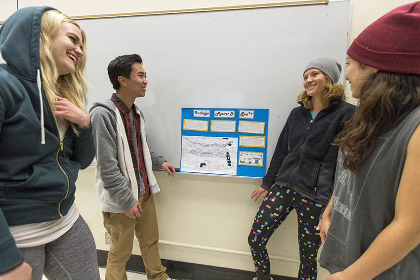 Students look at final project for Recreation Destination Resorts class