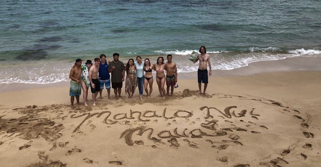 Students on Hawaiian beach with Mahalo written in sand