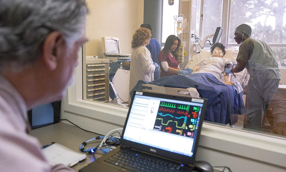 """SF State nursing students help a """"patient"""" in a simulated hospital room."""