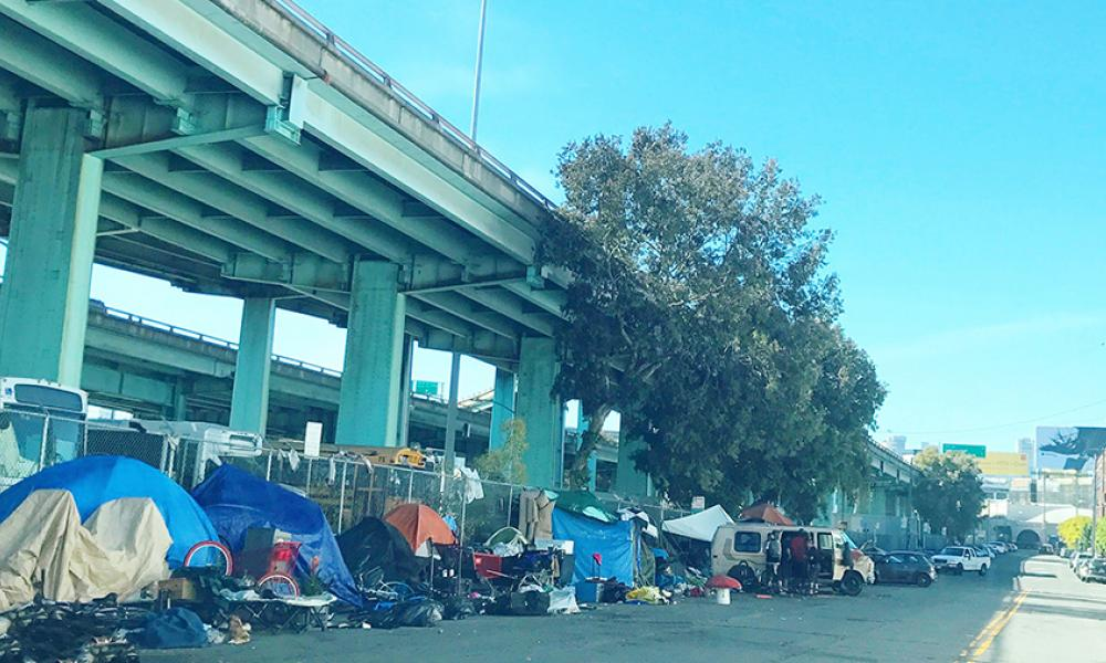 freeway overpass with tent encampment beneath