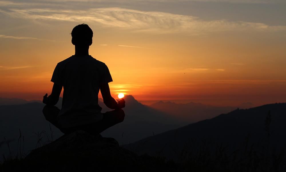 person meditating facing sunset