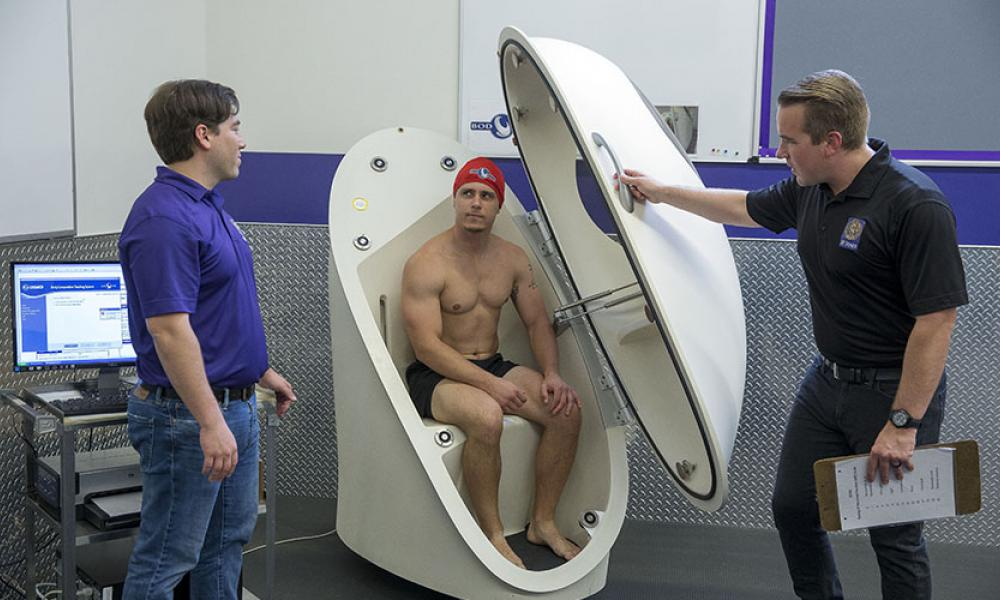 Ryan Durk and Jimmy Bagley pop Donny Frances Gregg into the BOD POD to evaluate his body composition.