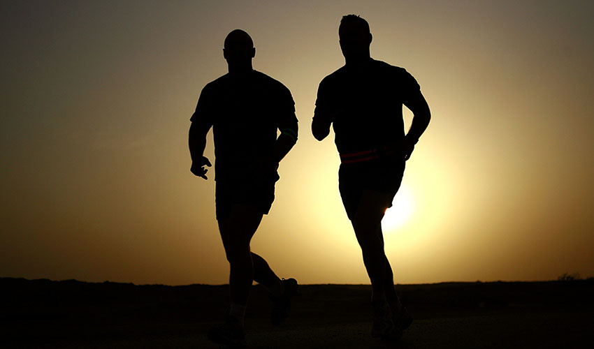 Two runners in front of the sunset